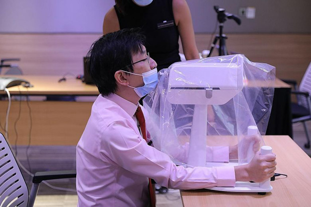​Dr Luke Tay, a consultant at SGH who was part of the team that developed the robot, demonstrating how a patient would position himself when undergoing a swab test done by the SwabBot.ST PHOTO ONG WEE JIN
